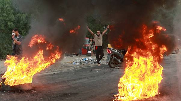 Image: Anti-government protesters set fires and close a street during a dem