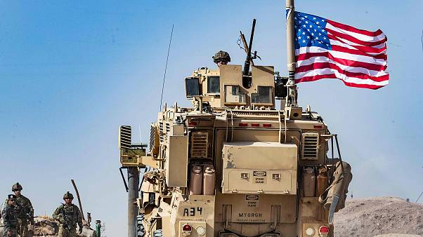 Image: A U.S. soldier sits atop an armoured vehicle during a demonstration