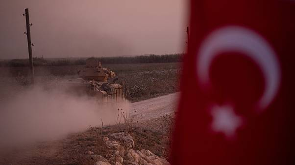 Image: A Turkish armored vehicle prepares to cross the border into Syria on