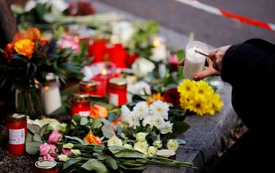 A woman lights a candle at a makeshift memorial in Halle, Germany Oct 10, 2019, after two people were killed in a shooting.
