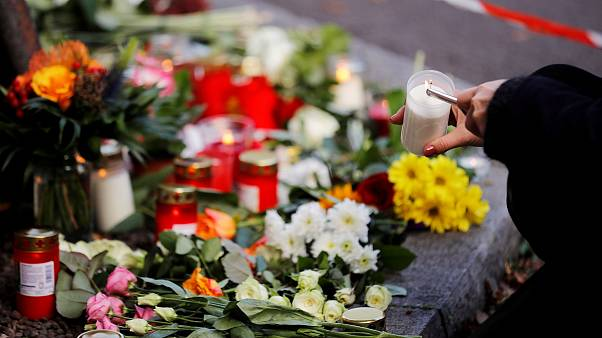 Image: A woman lights a candle at a makeshift memorial in Halle, Germany Oc