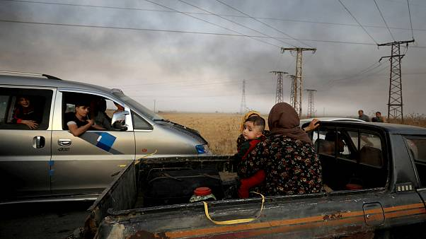 Image: A woman and her baby sit in the back of a truck as they flee Ras al-