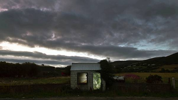 Image: A former customs guard hut is illuminated on the Irish border on Aug