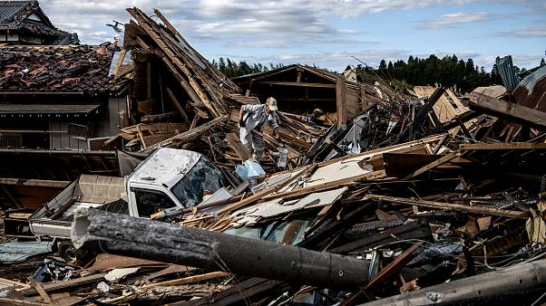Image: A man looks through debris of a building that was destroyed by a tor