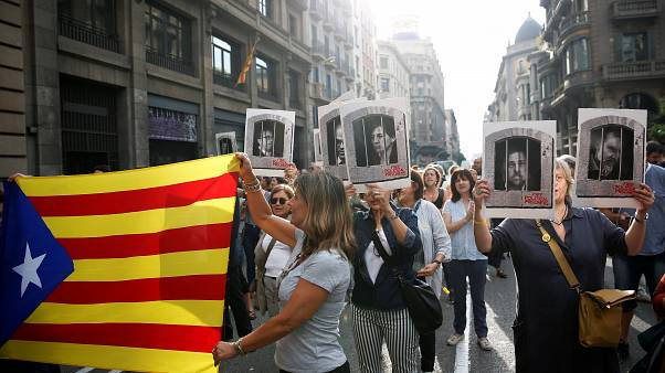 People holding an Estelada and pictures of Catalan politicians as they walk