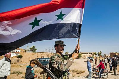 A Syrian regime soldier waves the national flag a street on the western entrance of the town of Tal Tamr in the countryside of Syria\'s northeastern Hasakeh province on Monday.