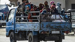 Image: Syrian families fleeing the battle zone between Turkey-led forces an