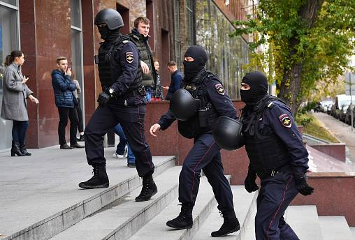 Image: Russian police officers walk to enter a business centre, which house