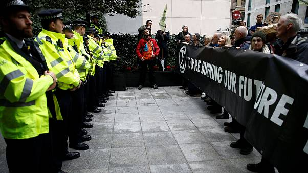 Image: Protesters hold a banner outside the BlackRock office during an Exti
