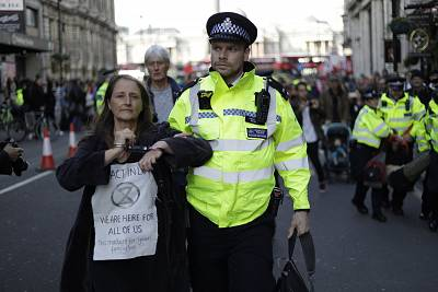 Police officers remove Extinction Rebellion climate change protesters who sat and blocked traffic on Whitehall at the bottom of Trafalgar Square, during a rally in London, Wednesday.