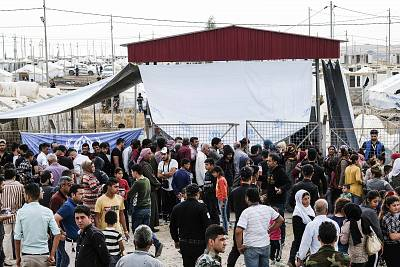Syrian refugees fleeing the Turkish incursion in Northern Syria wait to receive aid from the UNHCR and other International NGOs as more than 200 people arrive at the facility on Thursday in Dohuk, Iraq.