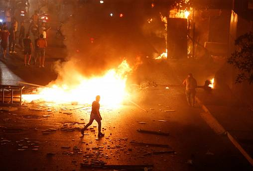 Image: A demonstrator walks close to a fire during a protest over deteriora