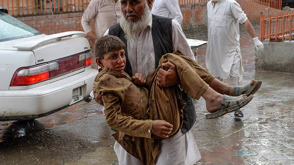 Image: A volunteer carries an injured youth to hospital, following a bomb b