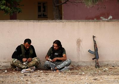 Turkey-backed Syrian rebel fighters pause before crossing into Syria on Thursday.