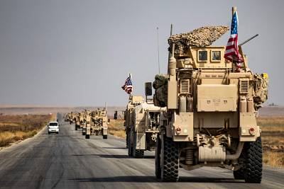 U.S. military vehicles drive on a street in the town of Tal Tamr Sunday after pulling out of their base.