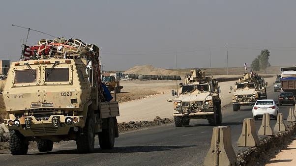 Image: A convoy of U.S. vehicles at the Iraqi-Syrian border crossing in the