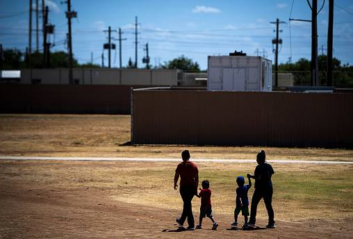 Image: Migrant women and children walk at the South Texas Family Residentia