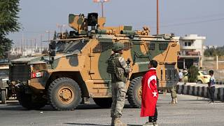 Boy wearing a Turkish flag stands next to a Turkish soldier in the town of