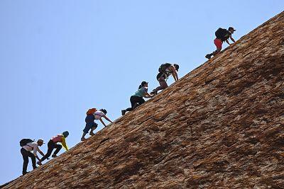 Tourists climb Uluru on Friday.