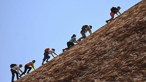 Image: Tourists climb Uluru.