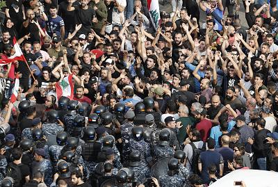 Hezbollah supporters stand in front of Lebanese riot policemen, as they shout slogans pro-Hezbollah leader Sayyed Hassan Nassrallah, during a protest near the government palace, in downtown Beirut, Lebanon on Oct. 25, 2019.