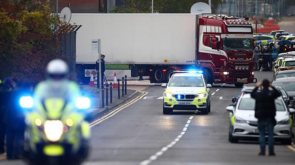 Image: Police officers drive away a lorry in which 39 dead bodies were disc