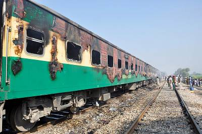 Burnt-out train carriages sit on the rails after a passenger train caught on fire in Punjab on Thursday.