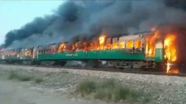 Image: The fire burns after a gas canister train passengers were using to c