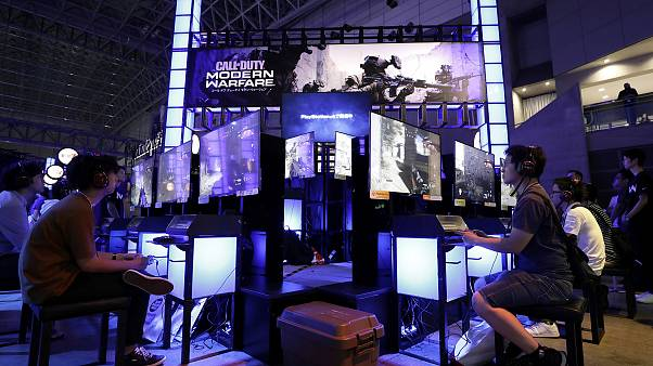 Image: Attendees use Sony Corp. PlayStation 4 (PS4) game consoles to play t