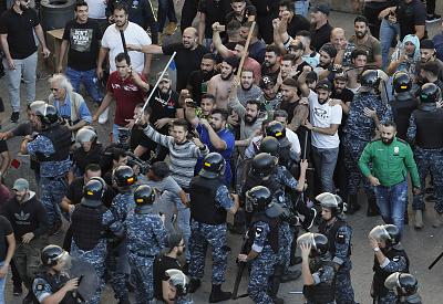 Riot police try to stop Hezbollah supporters who arrived to burn and destroy tents in the protest camp set up by anti-government protesters, in Beirut, Lebanon, on Tuesday.