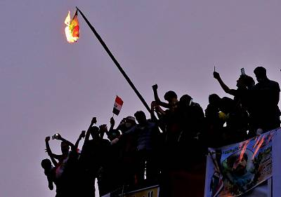 Iraqi anti-government protesters burn the Iranian flag during a demonstration in Baghdad, Iraq, on Tuesday.