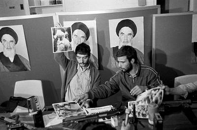 Ebrahim Asgharzadeh, left, a representative of the Iranian students who stormed the U.S. Embassy, holds up a photo of one of the blindfolded hostages, during a news conference in the embassy in Tehran on Nov. 5, 1979. Posters of Ayatollah Ruhollah Khomeini adorn the wall.