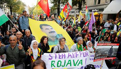 Kurdish protesters carry flags and a banner with a portrait of of jailed Kurdistan Workers Party (PKK) leader Abdullah Ocalan during a demonstration against Turkey's military action in northeastern Syria in Zurich, Switzerland Oct. 12.