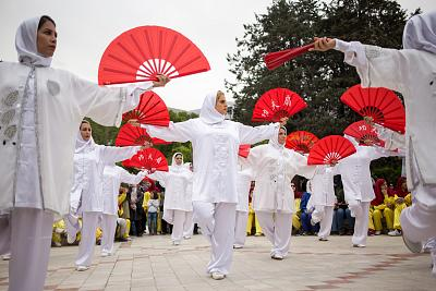 Doost, center, performs a fan form routine with fellow tai chi coaches in Niavaran Park in Tehran on April 27, 2018.