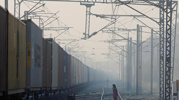 Image: A girl waits to cross the railway line on a smoggy morning in New De
