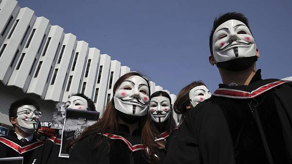 Image: University students wearing Guy Fawkes masks during a protest before