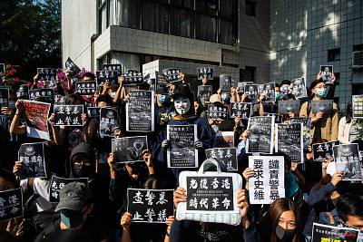 Protesters hold a photos of Chow Tsz-Lok during a memorial flash mob to remember him in Hong Kong on Friday.