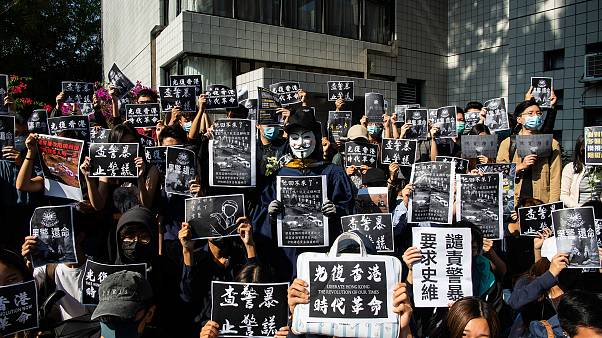 Image: Protesters hold a photos of Chow Tsz-Lok during a memorial flash mob