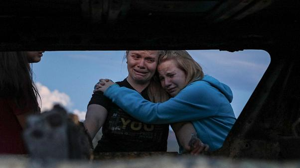 Image: Members of the Lebaron family mourn while they watch the burned car