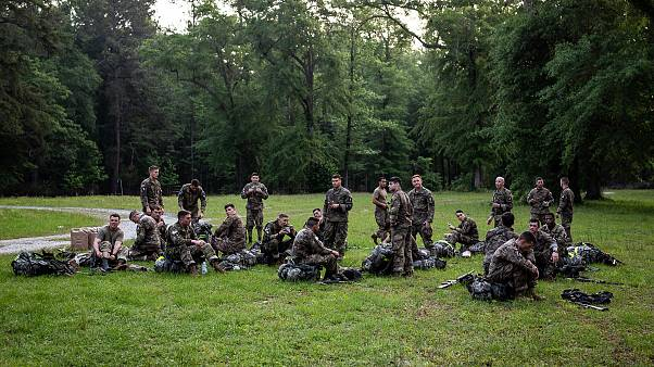 Army Ranger trainees rest after the 12-mile march during which they wore se