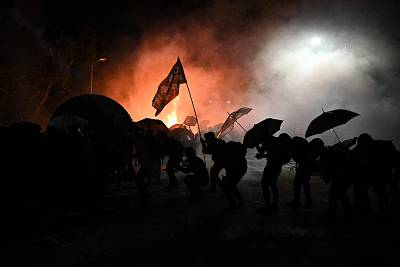 Protesters take cover during clashes with police at the Chinese University of Hong Kong (CUHK), in Hong Kong on Nov. 12, 2019.