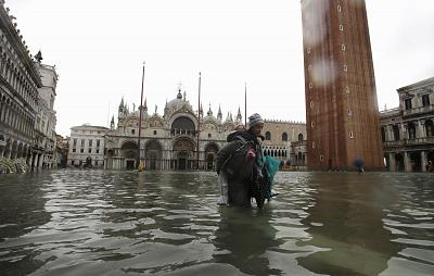 A woman carries her daughter in a flooded St. Mark\'s Square, in Venice, Italy, on Nov. 12, 2019.