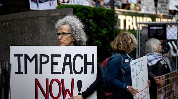 """A demonstrator with a sign reading """"Impeach now"""" takes part in Trumps Birth"""