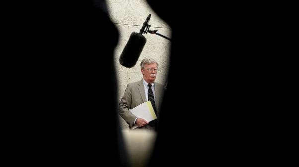 Image: National Security Adviser John Bolton listens in the Oval Office on