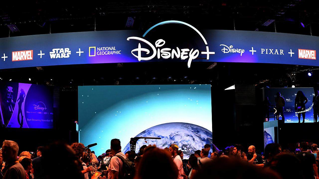 Image:m Attendees visit the Disney  streaming service booth at the D23 Expo