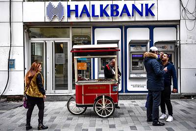 People walk by as a street vendor stands in front of a branch of the Turkish bank Halkbank on in Istanbul on Dec. 1, 2017.