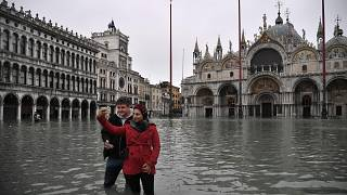 Image: People take selfies in flooded St. Mark's Square by St. Mark's Basil
