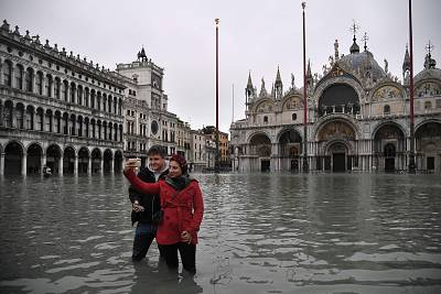 People take selfies in flooded St. Mark\'s Square by St. Mark\'s Basilica on Wednesday.