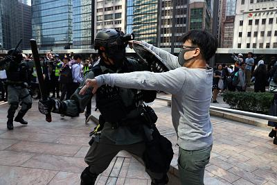 A riot police officer scuffles with an anti-government protester in Hong Kong\'s Central District on Wednesday.