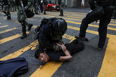 Police detain a man during a flash mob to block roads in Central on Wednesday.